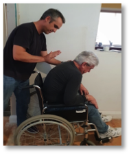 Demonstrating clearing a breathing obstruction from disabled person in wheelchair